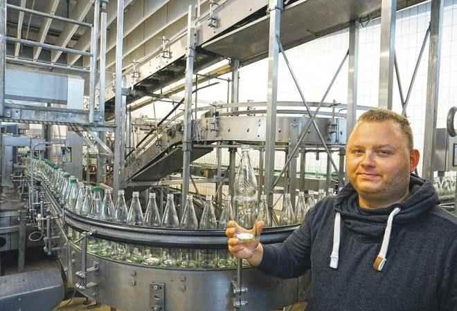 Rund 35 Millionen Flaschen befüllen die Wüteria Mineralquellen im Jahr. Die Mehrwegglasflasche, die Manuel Völkel präsentiert, kann 50 Mal wieder befüllt werden, bevor sie verschlissen ist. Foto: Friedemann Orths
